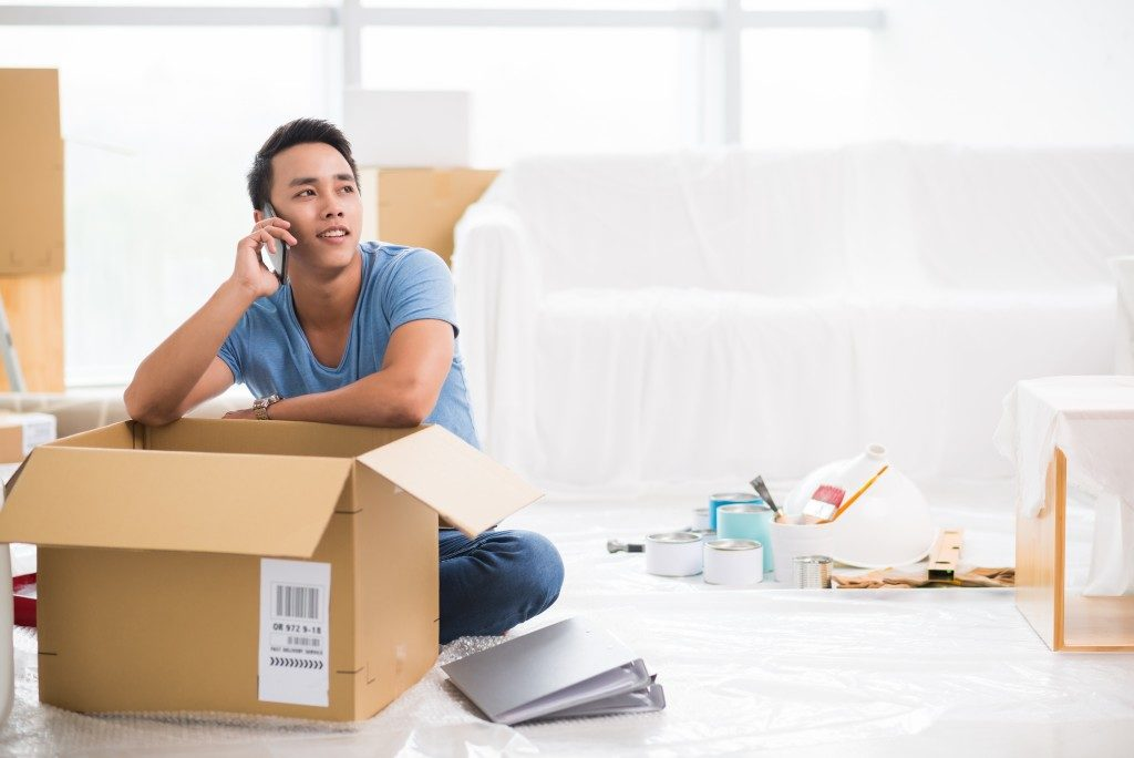 Man talking over the phone while packing