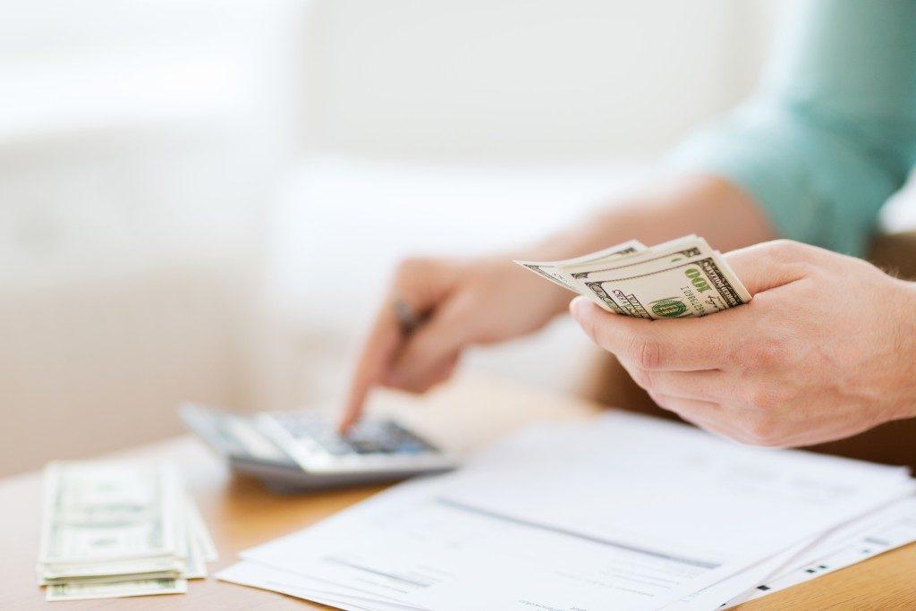 Person computing money using a calculator