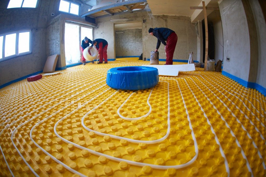 workers installing underfloor heating and cooling