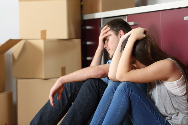 Angry evicted couple worried and sitting on the floor with hand on head