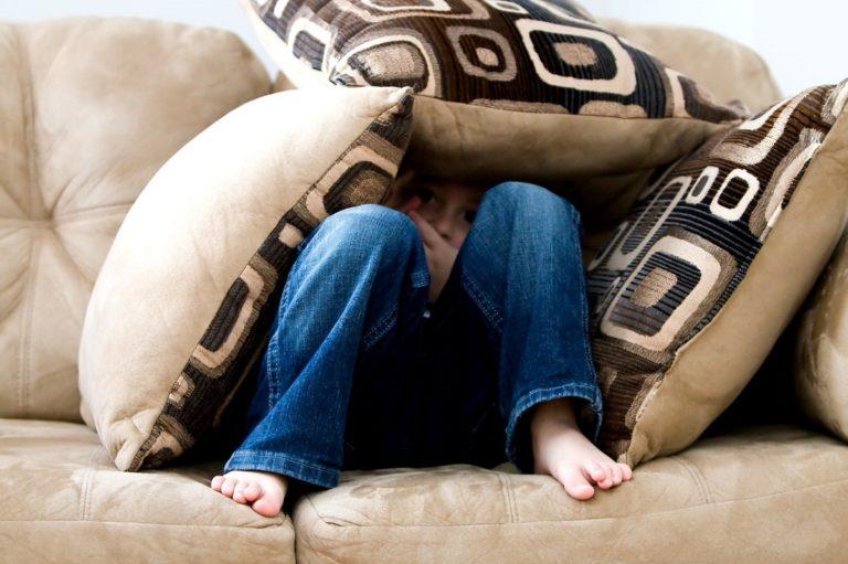Young boy hiding under the pillows