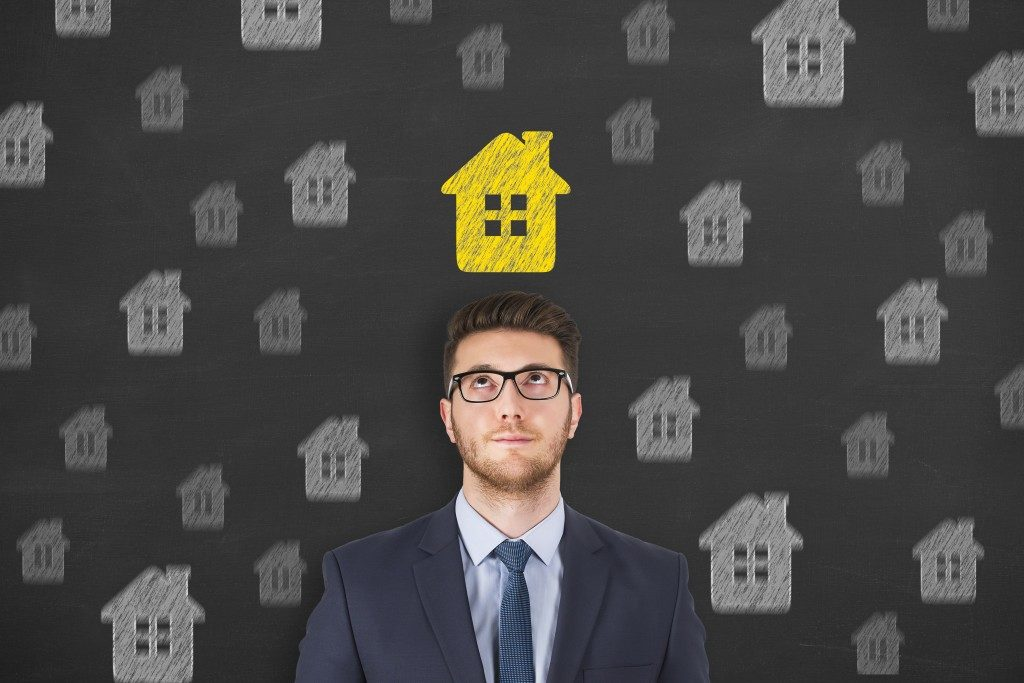 man with a yellow house above his head