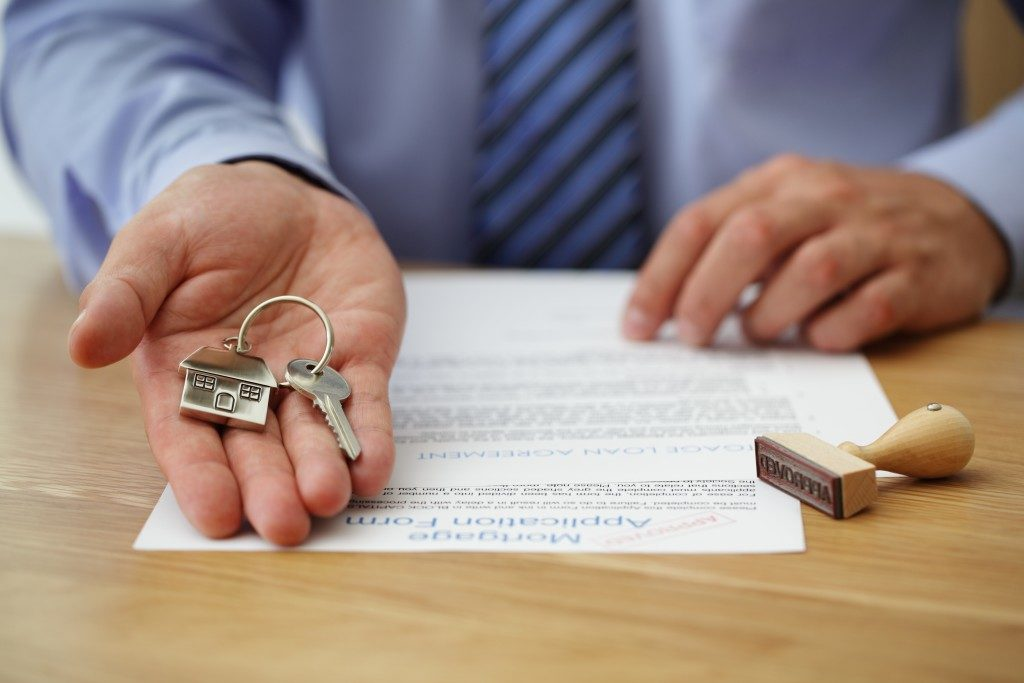 real estate agent handling house key with approved mortgage application