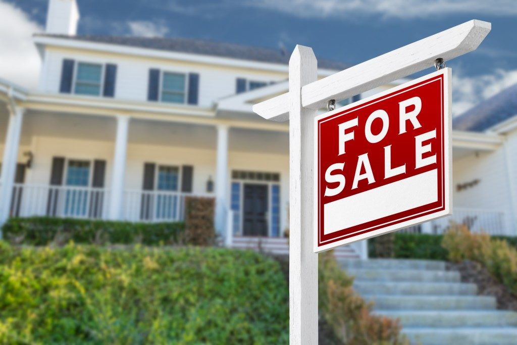 for sale signage in front of a suburban house