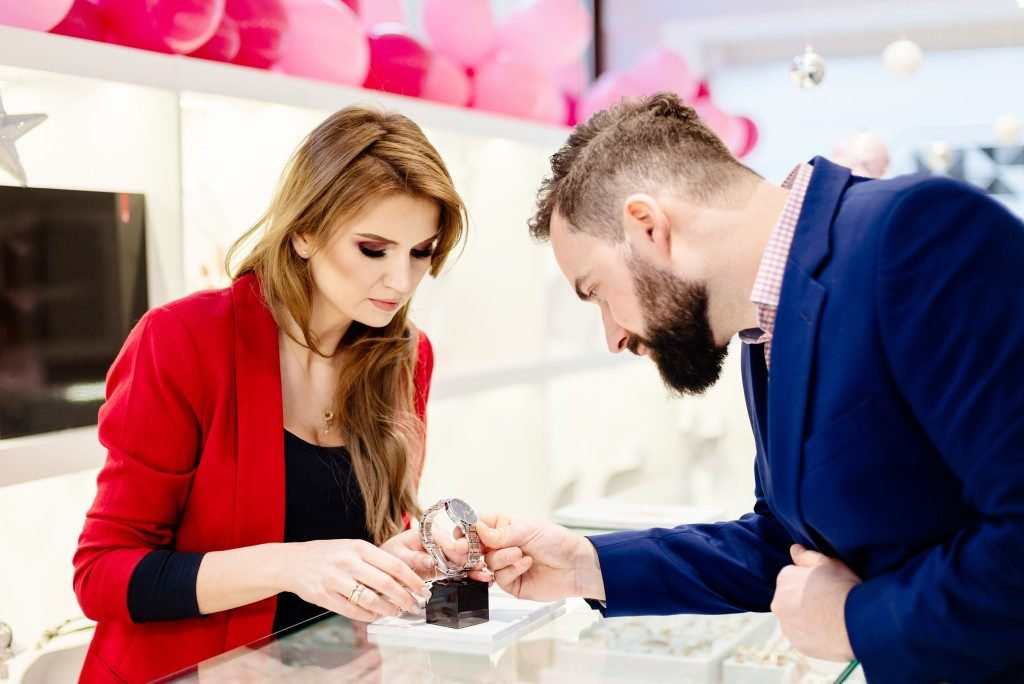 man looking a watch in a jewelry shop