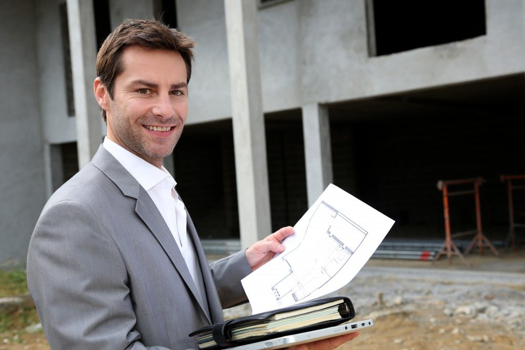 real estate agent holding a house design plan