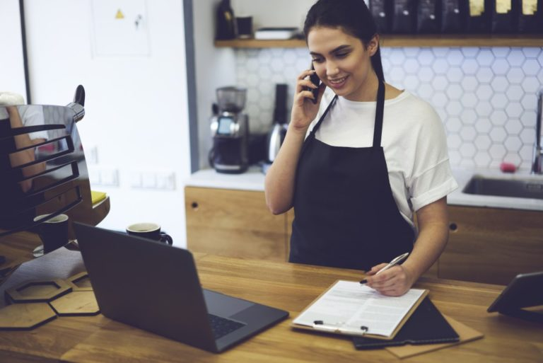 Entrepreneur dressed in black apron with mock up making coffee business by herself
