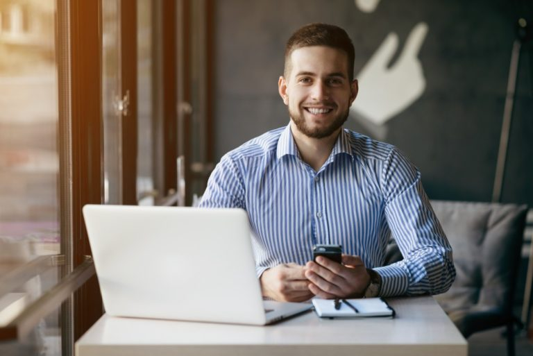 man working with his laptop and mobile phone