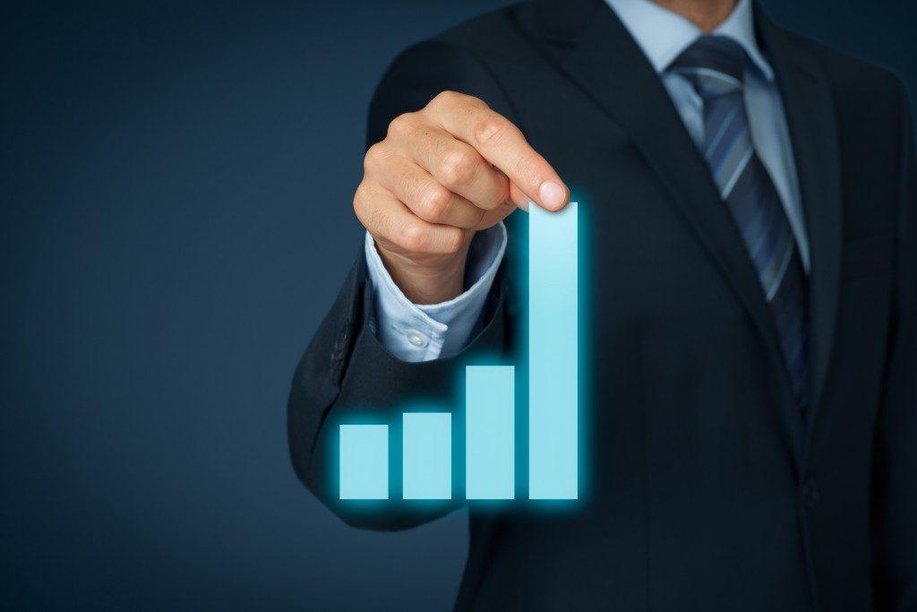 businessman holding a virtual bar graph