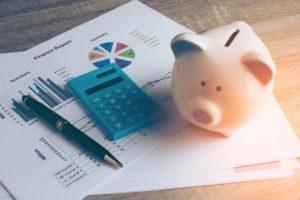 piggy bank, calculator, and pen