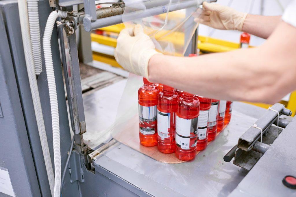 Factory worker packing full bottles into plastic film