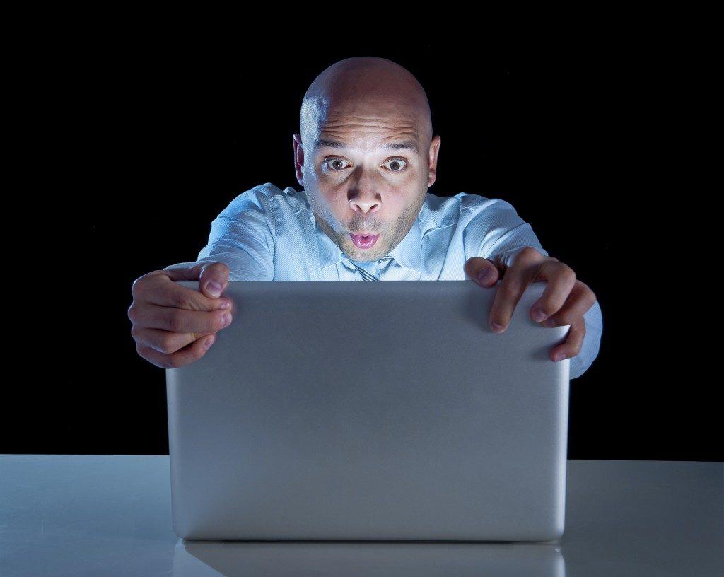 man clutching his laptop
