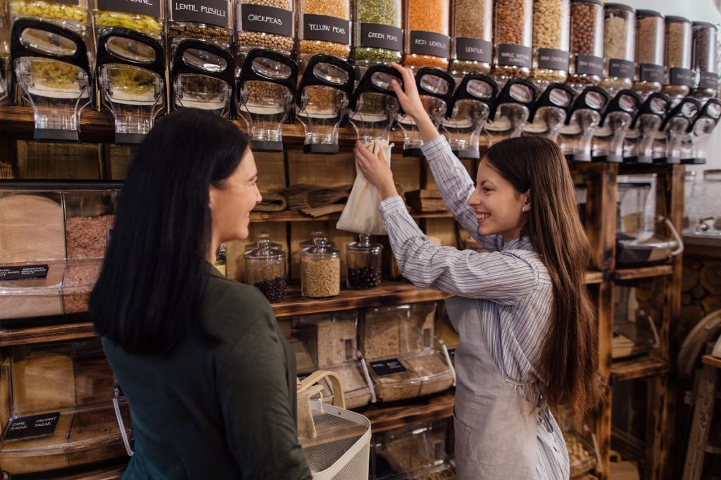Shop assistant helping customer in packaging free shop. Zero waste shopping - woman buying fresh products at package free grocery store.