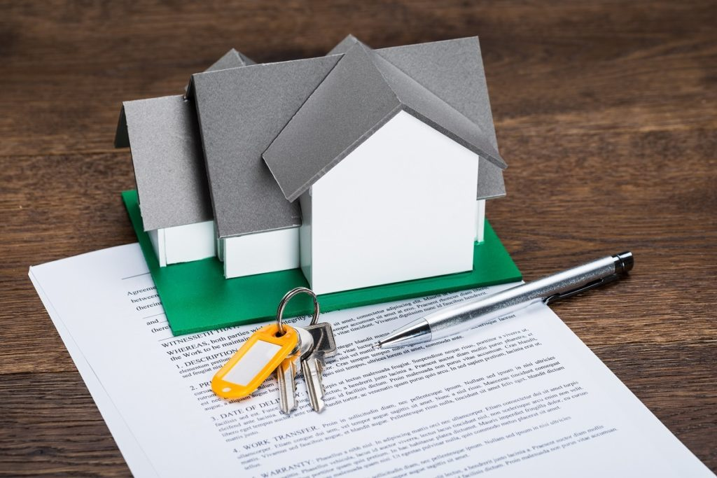 miniature house on top of a mortage loan document