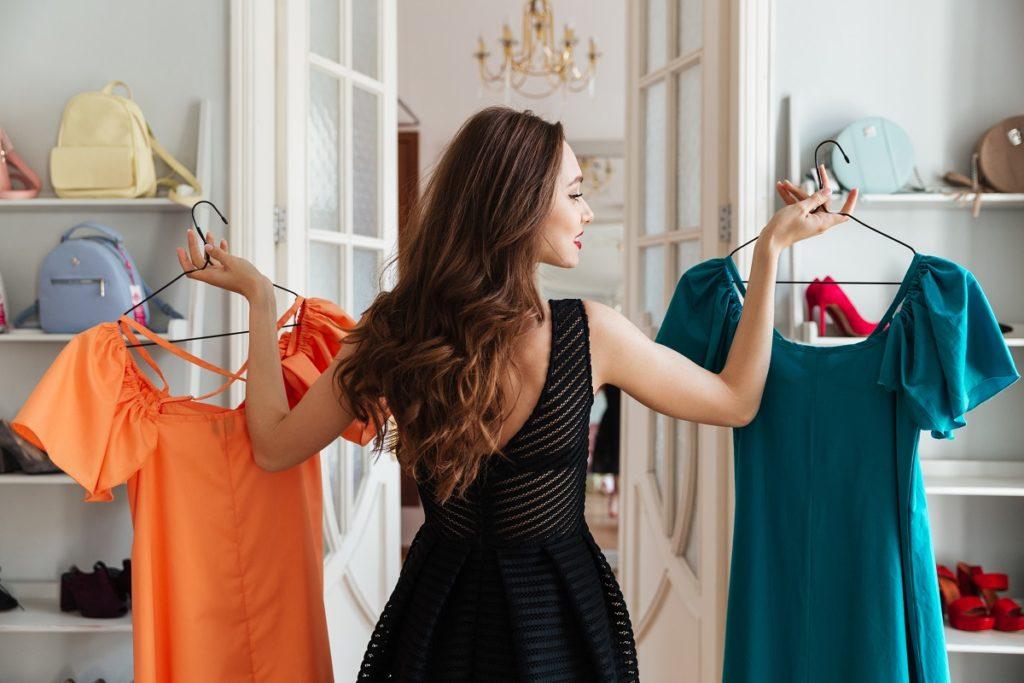 woman choosing between two dresses