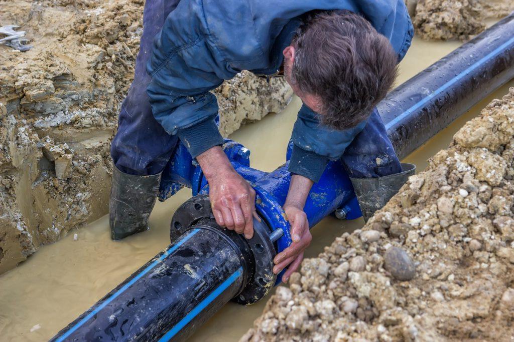 man installing underground pipe