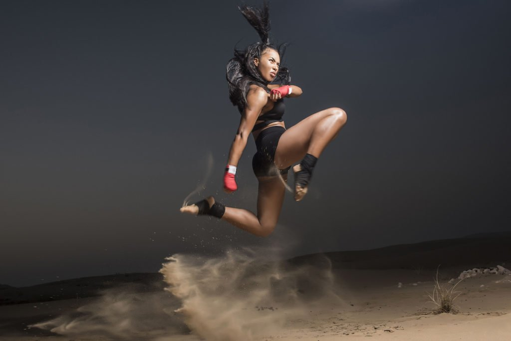 woman kickboxing in the sand
